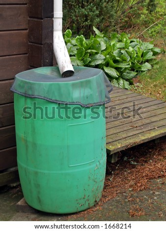 A water-butt to collect rain water, covered by net against - stock photo