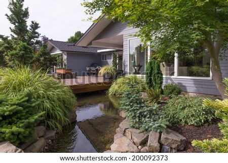A water feature emulating a creek flows under a deck and between landscaped rocks with a contemporary home in the background. - stock photo