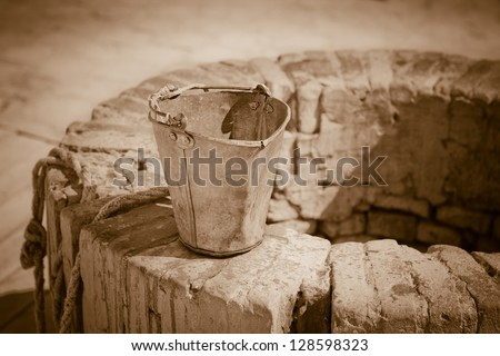 A water well with an old bucket. Vintage style photo. - stock photo