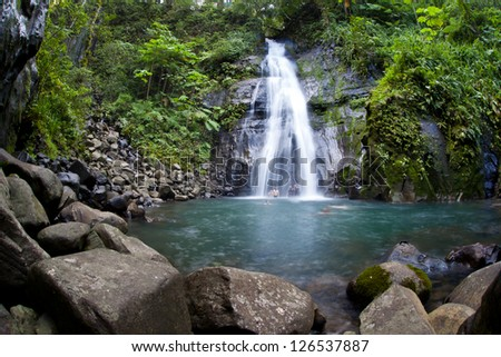 A waterfall cascades into a large pool on Cocos Island, Costa Rica.  Cocos is known for it large shark populations and great scuba diving. - stock photo