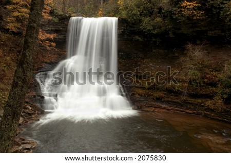 A waterfall deep in the forests of Virginia. Fall colors along the stream add to the beauty of the scene. - stock photo