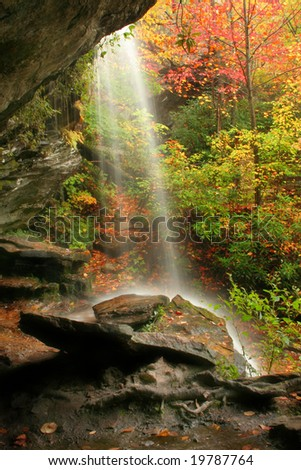 A waterfall during fall of the year. Captured on a rainy day. Used a long shutter speed to get a cotton candy effect on the water. - stock photo