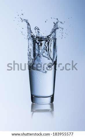 A Waterglass with falling ice cube splash with dew on blue background with reflection - stock photo