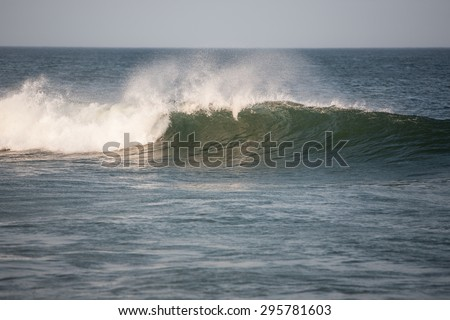 A wave breaks in shallow water near a beach on Cape Cod, Massachusetts.  - stock photo
