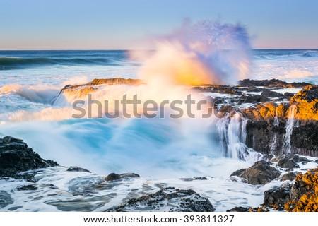 A wave crashed volcanic rocks near Thor's Well, Oregon - stock photo