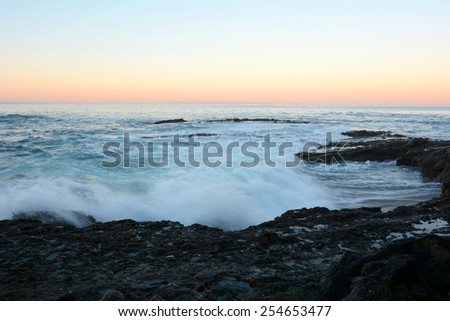A wave moves into shore and across a rocky reef during dawn - stock photo