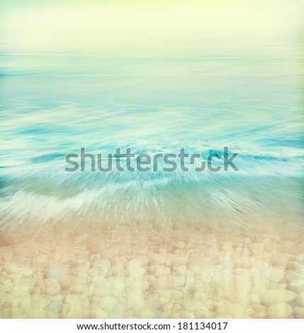 A wave of water washing over a rocky shoreline done with subtle retro colors.  Image made using panning motions combined with a long exposure. - stock photo