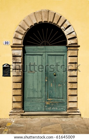 A weathered green double door with a stone arch in a yellow wall. - stock photo