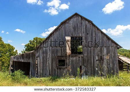 A weathered old barn in a field under cloudy skies, surrounded by overgrown grass and trees. - stock photo