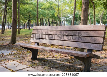 A Weathered Park Bench in the Park of The Kaohsiung City. Covered by Spots of Sunlight.  - stock photo