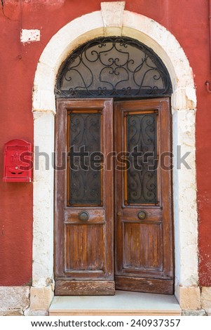 A weathered wooden door in an old red building - background - stock photo