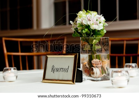 a wedding bouquet in a vase filled with water and sea shells on a reserved table - stock photo