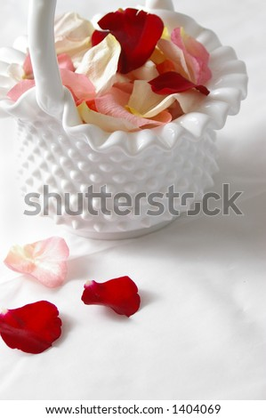 A wedding flower girl's basket with petals. - stock photo