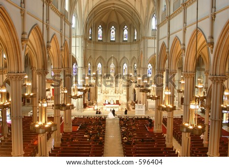 A wedding takes place inside an ornate church. - stock photo