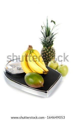 a weighing scale with fruits on a white background - stock photo