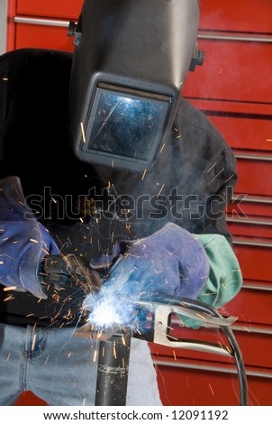 A welder fabricates a tool by attaching two pieces of metal. - stock photo