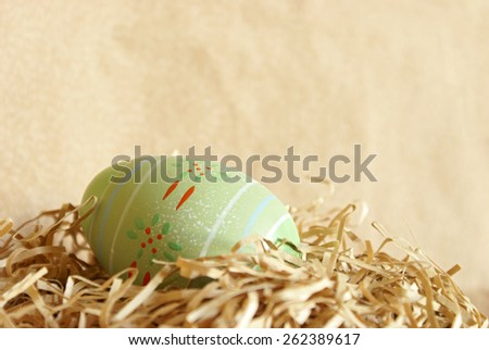 A well decorated Easter Egg hides in the pastel colored paper shred. - stock photo