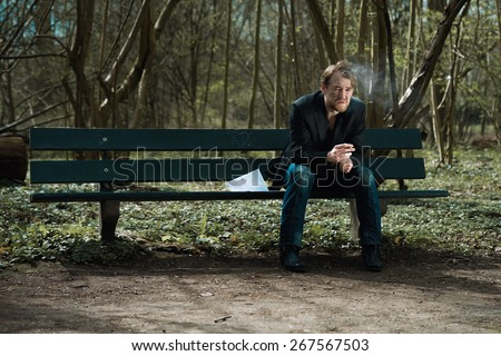 A well dressed depressed man sitting on a bench in a park smoking a cigarette with a suicide note next to him - stock photo