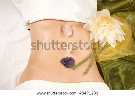 a wellness composition with a closeup of an abdomen of a natural mature woman with stones, flower and a silk scarf - stock photo