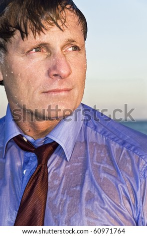 A wet businessman in his forties wearing a blue shirt and red tie. - stock photo