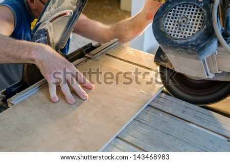 A wet saw cutter is being used to cut floor tile - stock photo
