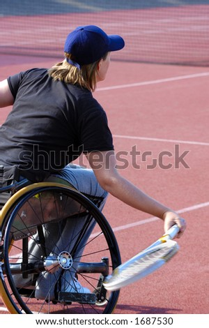 A wheelchair tennis player during a tennis championship match, returning a shot. Motion blur on her racket. - stock photo