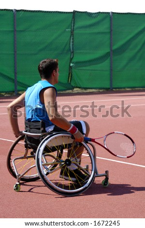 A wheelchair tennis player during a tennis championship match, waiting to take a shot. - stock photo