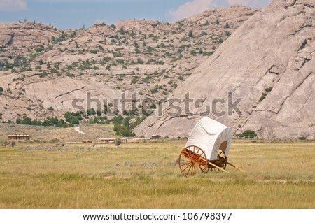 A white and brown covered handcart in a field in Wyoming - stock photo