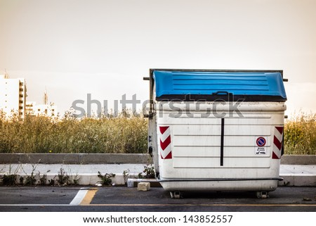 a white and weathered dumpster at the street side - stock photo