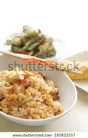 A white bowl full of rice with chopsticks beside it. - stock photo