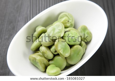 A white bowl on a wooden table with lima beans in it. - stock photo