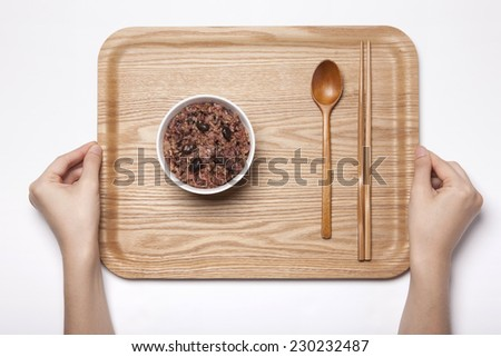A white bowl with multi-grain rice and wood tray, chopstick, female hands, spoon isolated white top view at the studio. - stock photo