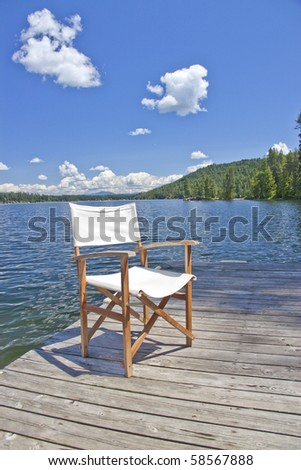 A white canvas chair on the dock of a beautiful lake with blue sky and clouds - stock photo