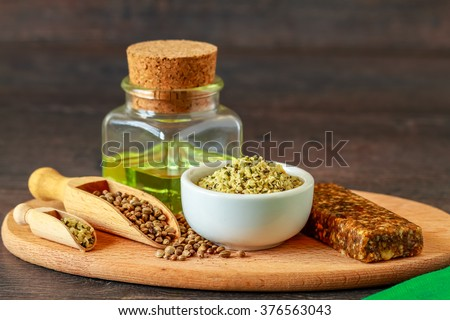 A white ceramic bowl full of shelled hemp, seeds and hemp oil - stock photo