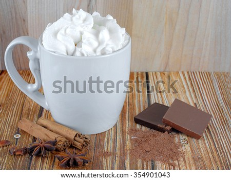 A white ceramic cup of coffee or cocoa topped with whipped cream on a rustic wooden table. Milk and dark chocolate, cinnamon, cocoa and star anise are scattered around. Horizontal image with copyspace - stock photo