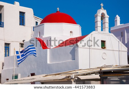 A white church with red roof and Greek flag at Greek town of Mykonos - stock photo