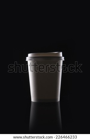 A white coffee take out container(cup) on the reflective bottom isolated black.  - stock photo
