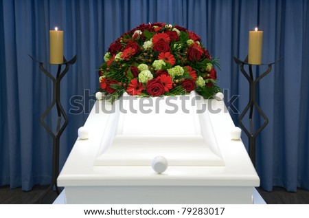 A white coffin in a mortuary with a flower-arrangement - stock photo