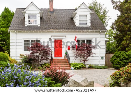 A White Cottage with Red Door in Canada - stock photo
