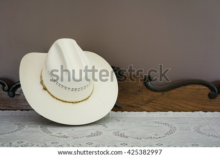 A White Cowboy Hat on an Antique Cabinet - stock photo