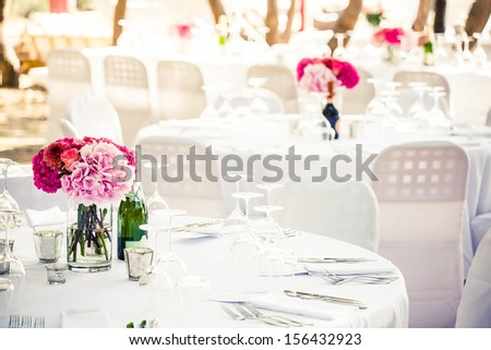 a white crisp decorated table with a pink hydrangea centerpiece and multiple other decorated tables in the background - stock photo