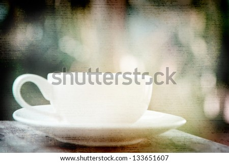 a white cup of black coffee in garden background - stock photo