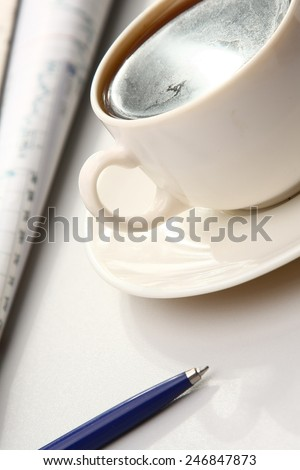 A white cup of cappuccino and a blue pen on paper table numbers - stock photo