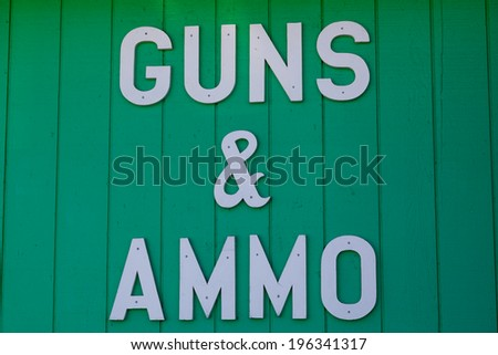 A white cutout letter sign nailed to a wall of a gun shop advertising guns and ammo for sale. - stock photo