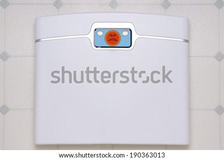 A white, digital bathroom scale displaying a sad face emoji. - stock photo