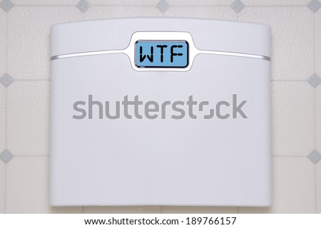 A white digital bathroom scale displaying the text message WTF. - stock photo