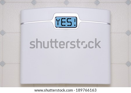 A white digital bathroom scale displaying the text message YES. - stock photo