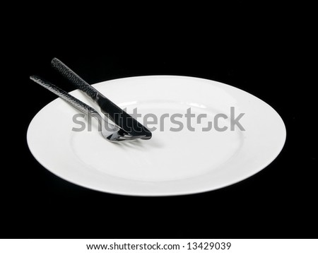 A white dinner plate with knife and fork - stock photo