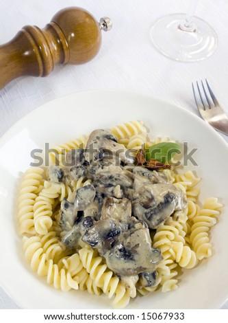 A white dish of fusilli with a mushroom cream. Focus on the pasta. - stock photo