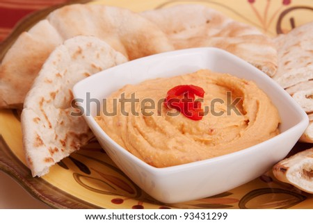 A white dish with red pepper hummus. Pita bread in the background. - stock photo